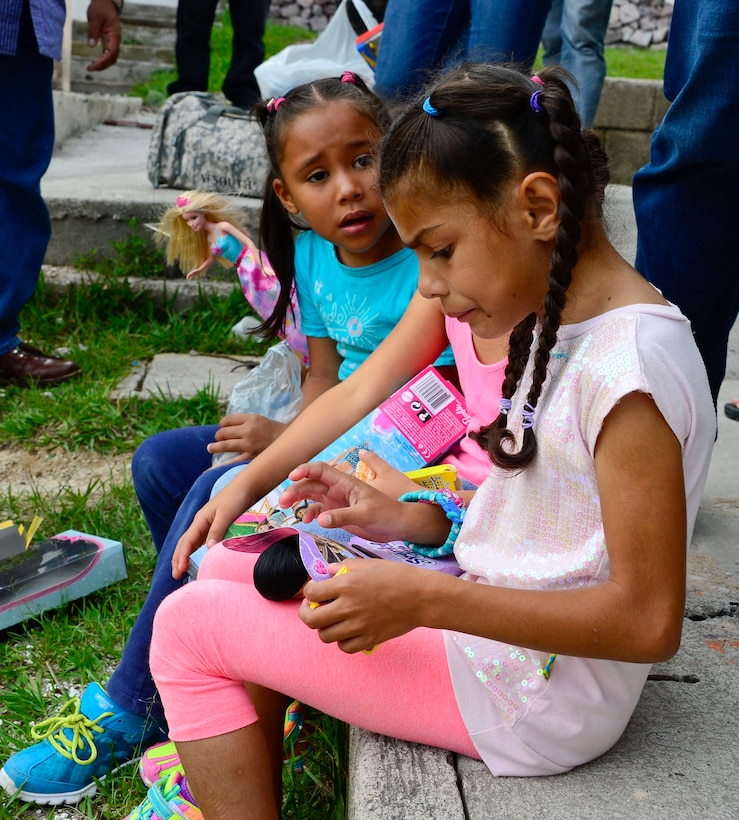 Young girls from the Casa de Corderitos orphanage in Tegucigalpa, Honduras play with their new Barbie dolls, June 18, 2015. The 12th AF (AFSOUTH) members spent some of their downtime during a three-day assessment visit to Honduras Air Bases to volunteer with the local community and to deliver toys and candy that were donated businesses in Tucson, Ariz. (U.S. Air Force photo by Tech. Sgt. Heather R. Redman/Released)