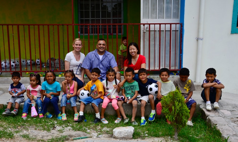 U.S. Air Force Staff Sgt. Katie Adams, Master Sgt. Roberto Vasquez and Capt. Sarah Hartenstein, 12th AF (AFSOUTH) take a group photo with the children at Casa de Corderitos orphanage in Tegucigalpa, Honduras, June 18, 2015. The 12th AF (AFSOUTH) members spent some of their downtime during a three-day assessment visit to Honduras Air Bases to volunteer with the local community and to deliver toys and candy that were donated by businesses in Tucson, Ariz. (U.S. Air Force photo by Tech. Sgt. Heather R. Redman/Released)