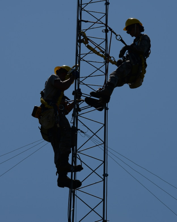 Airman 1st Class Mark Dunton (left) and Senior Airman Samantha Maquillan are silhouetted against the late morning sun as they work on upgrading lightning protection and grounding on a communications tower at Pease Air National Guard Base, N.H., on June 22, 2015. The installation of the lightning protection gear helps protect resources such as radios that 157th Air Refueling Wing Airmen use to support the mission. The Airmen are assigned to the 243rd Engineering Installation Squadron, Maine Air National Guard in South Portland, Maine.  (U.S. Air National Guard photo by Staff Sgt. Curtis J. Lenz)