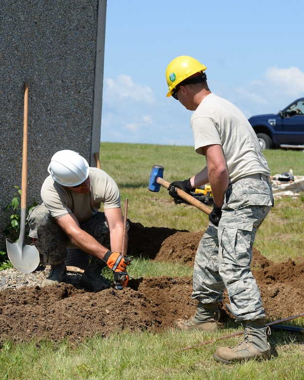 Master Sgt. Jason Bowen, team chief (left) steadies a grounding rod as Senior Airman Alexander Russo uses a sledge hammer to drive a grounding rod into the ground as part of lightning protection and grounding upgrades on communications equipment at Pease Air National Guard Base, N.H., on June 22, 2015. The installation of the lightning protection gear helps protect resources such as radios that 157th Air Refueling Wing Airmen use to support the mission.   The Airmen are assigned to the 243rd Engineering Installation Squadron, Maine Air National Guard in South Portland, Maine.  (U.S. Air National Guard photo by Staff Sgt. Curtis J. Lenz)