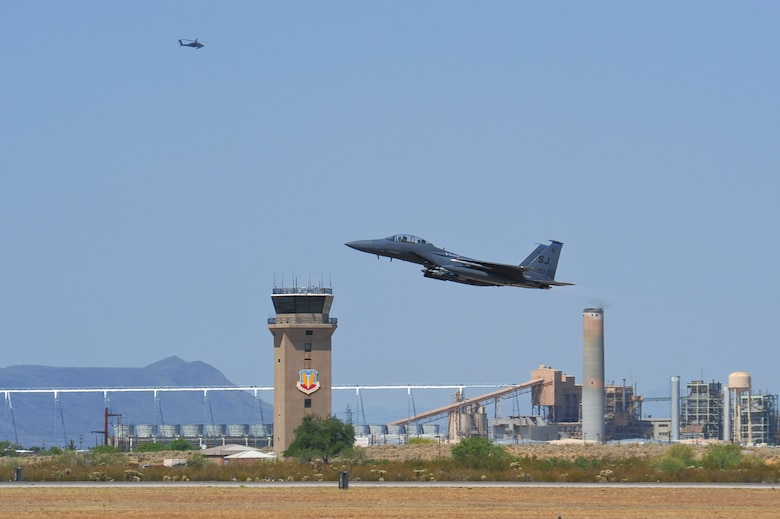 An F-15E Strike Eagle from the 334th Fighter Squadron, Seymour Johnson Air Force Base, N.C., takes off from the runway at Davis-Monthan AFB, Ariz., while a helicopter flies by June 22, 2015. Fourteen F-15E Strike Eagles from Seymour Johnson AFB trained with F-35A Lightning IIs, F-16 Fighting Falcons and A-10 Thunderbolt IIs throughout southern Arizona's military operating areas.  (U.S. Air Force photo by Airman 1st Class Chris Massey/Released)