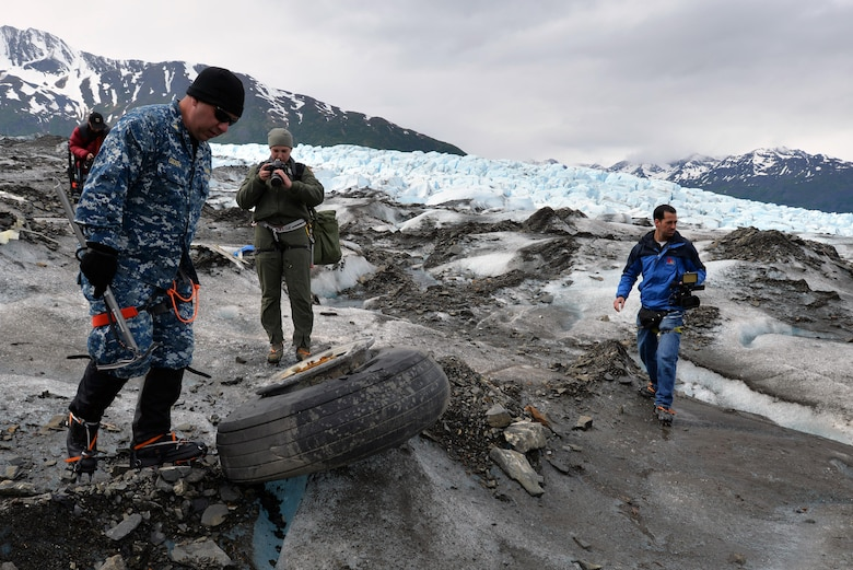 Navy Lt. Cmdr. Paul Cocker (left), the Alaskan Command deputy chief of future operations and Operation Colony Glacier project officer, shows local media some of the aircraft debris from the 1952 C-124 Globemaster II accident, June 10, 2015. Each summer since 2012, ALCOM has supported Operation Colony Glacier by removing aircraft debris and assisting in the recovery of human remains to ensure closure for families who have lost loved ones. (U.S. Air Force photo/Tech. Sgt. John Gordinier)