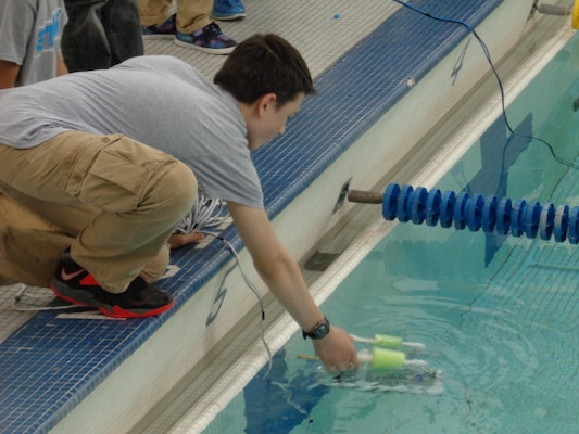 A SeaPerch contestant launches his remotely operated vehicle to complete in the underwater obstacle course during regional competition in Philadelphia.