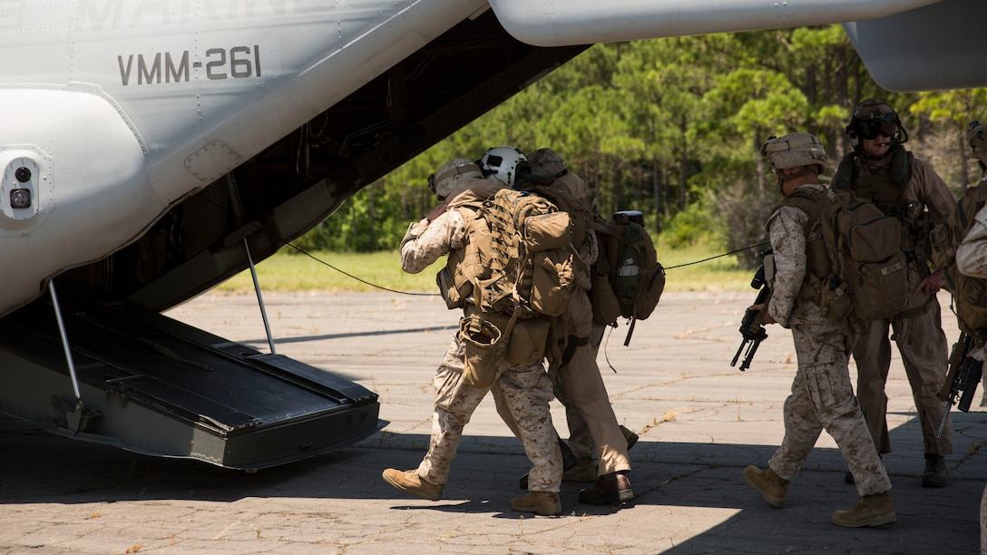 Marines with Lima Co., 3rd Battalion, 8th Marine Regiment, guide a role player acting as a downed pilot to an MV-22B Osprey during a tactical recovery of aircraft and personnel exercise aboard Marine Corps Outlying Landing Field Atlantic, N.C., June 19, 2015. Due to the short notice nature of TRAP missions, the Marines stood by during the week to receive the mission, showing them the importance of maintaining readiness. The TRAP exercise was part of Special Purpose Marine Air-Ground Task Force Crisis Response-Africa's certification exercise, the final step in their pre-deployment training. (U.S. Marine Corps photo by Cpl. Justin T. Updegraff/ Released)