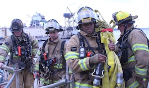 Members of JFRD haul equipment on board USS Tornado during a fire drill at the BAE Systems shipyard.  The local fire department was called in to augment the ship's crew and BAE first responders as a test of their ability to work together in a challenging shipyard environment.