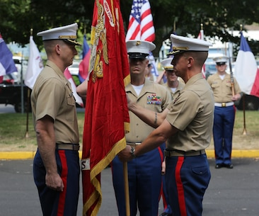 U.S. Marine Corps Maj. Joel C. Schumacher, off going commanding officer, Recruiting Station Portland (RS PRT), passes the Marine Corps Colors to Maj. Brooks W. Boehlert, oncoming commanding officer, RS PRT, to signify the change of command for RS PRT at 6th Engineer Support Battalion, June 19. (U.S. Marine Corps photo by Sgt. Tyler C. Vernaza / released)