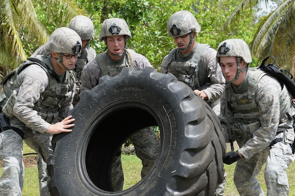 Airmen from the 36th Security Forces Squadron flip a tire during the Defender Challenge June 22, 2015, at Andersen Air Force Base, Guam. Airmen tested their physical and mental strength through various obstacles and challenges during the competition, ending with a live-fire shooting course. (U.S. Air Force photo by Airman 1st Class Joshua Smoot/Released)