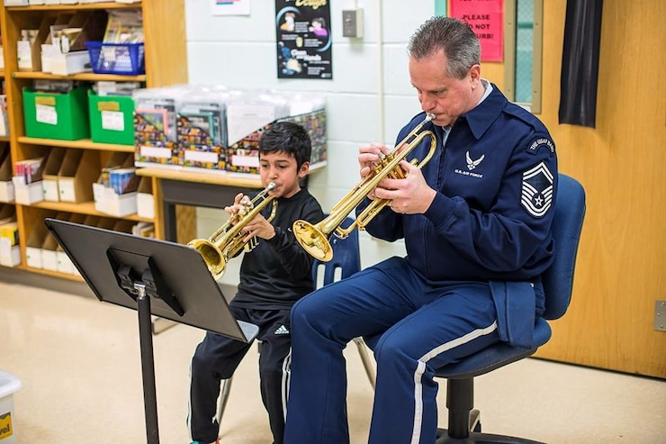 For the entire school year our Advancing Innovation through Music (AIM) program supported local educational outreach program Bridges: Harmony Through Music.  We were honored to be presented the Community Partner of the Year award by founding director Bonny Tynch.  Pictured is Senior Master Sergeant Kevin Burns working with a young trumpet student at a Bridges event.  (U.S. Air Force Photo/released)