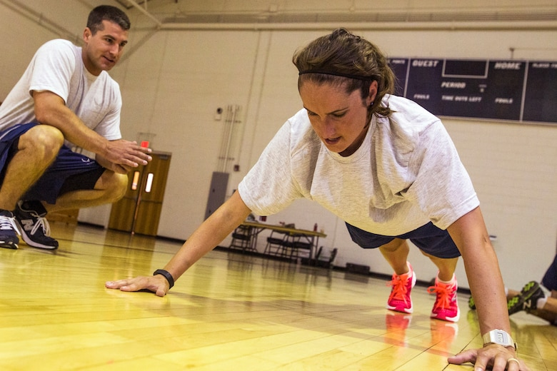 Senior Airman Andrew C. King, left, counts Senior Airman Ashley V. Chytraus's pushups during the United States Air Force Fitness Test at Joint Base McGuire-Dix-Lakehurst, N.J., June 14, 2015. Both King and Chytraus serve in the 108th Wing, New Jersey Air National Guard. Chytraus was in a motorcycle accident June 21, 2014. The collision broke two vertebrae in Chytraus's neck, crushed her hand, mangled the quadriceps tendon in her leg, forced two splintered ribs into her liver and fractured her elbow. In addition, she died while being medevaced to the hospital. 358 days later, she passed all portions of the Air Force Physical Fitness Test and received an excellent. (U.S. Air Force photo by Master Sgt. Mark C. Olsen/Released)