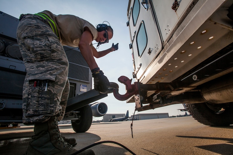 Senior Airman Ashley V. Chytraus, a crew chief with the 108th Wing, New Jersey Air National Guard, latches an air conditioning cart in preparation for a training flight at Joint Base McGuire-Dix-Lakehurst, N.J., June 11, 2015. Chytraus was in a motorcycle accident June 21, 2014. The collision broke two vertebrae in Chytraus's neck, crushed her hand, mangled the quadriceps tendon in her leg, forced two splintered ribs into her liver and fractured her elbow. In addition, she died while being medevaced to the hospital. 358 days later, she passed all portions of the Air Force Physical Fitness Test and received an excellent. (U.S. Air Force photo by Master Sgt. Mark C. Olsen/Released)