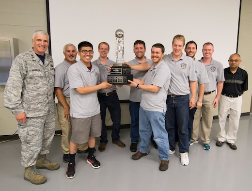 Cutline: Maj. Gen. Thomas J. Masiello, Air Force Research Laboratory commander, presents the team from Wright-Patterson Air Force Base the 2015 AFRL Commanders Challenge Trophy after they were named the winners June 19 at the Muscatatuck Urban Training Center in Butlerville, Indiana. The challenge involved four teams from Wright-Patterson AFB; Robbins AFB, Ga.; Hill AFB, Utah; and Kirtland AFB, N.M., who were given the task to develop systems for detecting an active shooter. (Air Force photo by Wesley Farnsworth)