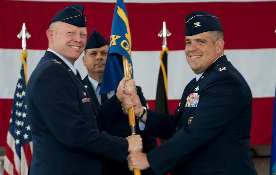 U.S. Air Force Col. Joe McFall, 52nd Fighter Wing commander, left, passes the ceremonial guidon to U.S. Air Force Col. Stephen Scherzer, incoming 52nd Maintenance Group commander, right, during the 52 MXG change of command ceremony in Hangar 1 on Spangdahlem Air Base, Germany, June 18, 2015. Scherzer served as Deputy Commander of the 83rd Training Group at Sheppard Air Force Base, Texas before arriving to Spangdahlem. (U.S. Air Force photo by Airman 1st Class Timothy Kim/Released)