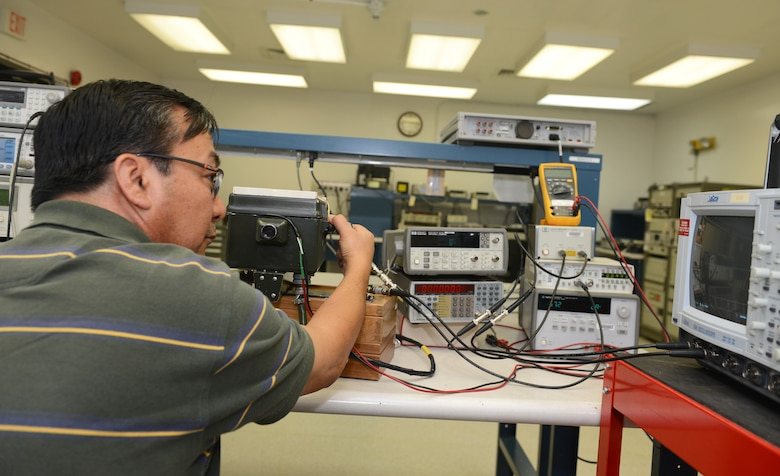 Oscar Cabatic, 36th Maintenance Squadron Precision Measurement Equipment Laboratory technician, analyzes a signal using a transponder test set, a spectrum analyzer, and a peak power meter June 19, 2015, at Andersen Air Force Base, Guam.  PMEL technicians ensure all the equipment they calibrate on a daily basis is accurate and reliable for the many units they support. (U.S. Air Force photo by Airman 1st Class Arielle Vasquez/Released)