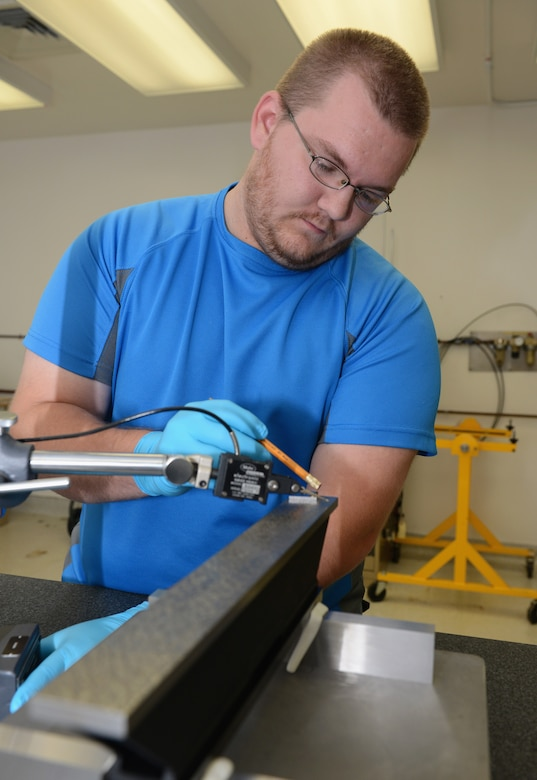 Elijah Bacchus, 36th Maintenance Squadron Precision Measurement Equipment Laboratory technician, calibrates the flatness of the base of a master level June 19, 2015, at Andersen Air Force Base, Guam. PMEL technicians calibrate anything from scales, digital voltmeters and generators to provide reliable equipment for the units they support.  (U.S. Air Force photo by Airman 1st Class Arielle Vasquez/Released)