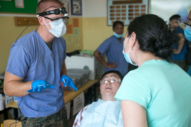 U.S. Navy Lt. Phillip Jakubowicz, left, speaks to a Mongolian interpreter about dental procedures he will perform on the Mongolian patient as part of the health services support engagement during Khaan Quest 2015 at the 79th High School in Ulaanbaatar, Mongolia, June 21. Khaan Quest is a regularly scheduled, multinational exercise hosted annually by the Mongolian Armed Forces and co-sponsored by U.S. Army, Pacific, and U.S. Marine Corps Forces, Pacific. Jakubowicz is a dental officer with 3rd Dental Battalion, 3rd Marine Logistics Group, III Marine Expeditionary Force.