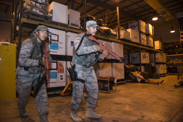 U.S. Air Force Senior Airmen Julian Solis and Morgan Esquerra search a medical warehouse for an active shooter after responding to a simulated 911 call during a battle drill June 19, 2015, at Al Udeid Air Base, Qatar. Several agencies of the 379th Air Expeditionary Wing were tested on their reaction to a possible active shooter scenario if an on-base incident truly ever occurred. (U.S. Air Force photo by Tech. Sgt. Rasheen Douglas)