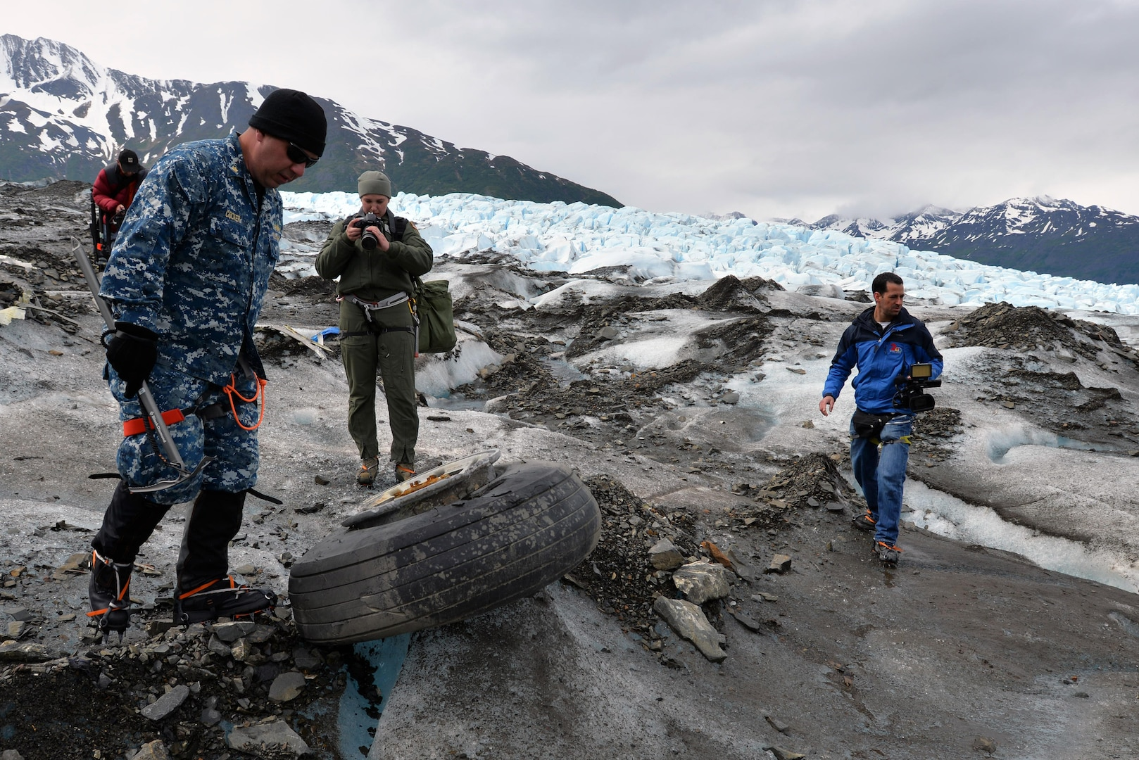 Navy Lt. Cmdr. Paul Cocker, left, the Alaskan Command deputy chief of future operations and Operation Colony Glacier project officer, shows local media some of the aircraft debris from the 1952 C-124 Globemaster II accident, June 10, 2015. Each summer since 2012, ALCOM has supported Operation Colony Glacier by removing aircraft debris and assisting in the recovery of human remains.