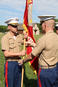 Maj. Geoffry M. Hollopeter passes the Marine Corps Colors to Maj. John P. Harley to signify the change of command for Recruiting Station Indianapolis at Fort Harrison State Park, Indianapolis June 24, 2015.