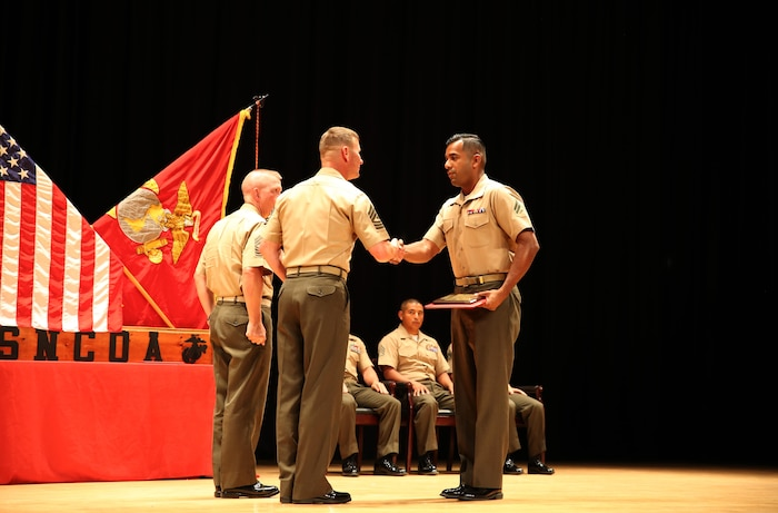 Cpl. Jose A. Cabrera, right, rifleman, Company A, Ground Combat Element Integrated Task Force, is congratulated by 1st Sgt. John D. Dober, center, first sergeant, Co. A, GCEITF, and guest speaker, during the Corporal's Course graduation at the Marine Corps Base Camp Lejeune Theater, June 24, 2015. Cabrera was selected as the recipient of the Gung-Ho Award. From October 2014 to July 2015, the GCEITF conducted individual and collective level skills training in designated ground combat arms occupational specialties in order to facilitate the standards-based assessment of the physical performance of Marines in a simulated operating environment performing specific ground combat arms tasks. (U.S. Marine Corps photo by Cpl. Paul S. Martinez/Released)