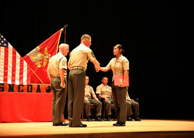 Cpl. Alicia Hernandez, right, combat engineer, Headquarters and Service Company, Ground Combat Element Integrated Task Force, is congratulated by 1st Sgt. John D. Dober, center, first sergeant, Company A, GCEITF, and guest speaker, during the Corporal's Course graduation at the Marine Corps Base Camp Lejeune Theater, June 24, 2015. Hernandez was selected as the recipient of the Physical Fitness Award. From October 2014 to July 2015, the GCEITF conducted individual and collective level skills training in designated ground combat arms occupational specialties in order to facilitate the standards-based assessment of the physical performance of Marines in a simulated operating environment performing specific ground combat arms tasks. (U.S. Marine Corps photo by Cpl. Paul S. Martinez/Released)