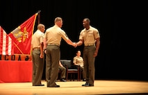 Cpl. Giovanni D. Destin, right, rifleman, Company A, Ground Combat Element Integrated Task Force, is congratulated by 1st Sgt. John D. Dober, center, first sergeant, Co. A, GCEITF, and guest speaker, during the Corporal's Course graduation at the Marine Corps Base Camp Lejeune Theater, June 24, 2015. From October 2014 to July 2015, the GCEITF conducted individual and collective level skills training in designated ground combat arms occupational specialties in order to facilitate the standards-based assessment of the physical performance of Marines in a simulated operating environment performing specific ground combat arms tasks. (U.S. Marine Corps photo by Cpl. Paul S. Martinez/Released)