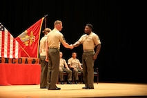 Cpl. Matiyes Kinker, right, assaultman, Weapons Company, Ground Combat Element Integrated Task Force, is congratulated by 1st Sgt. John D. Dober, center, first sergeant, Company A, GCEITF, and guest speaker, during the Corporal's Course graduation at the Marine Corps Base Camp Lejeune Theater, June 24, 2015. From October 2014 to July 2015, the GCEITF conducted individual and collective level skills training in designated ground combat arms occupational specialties in order to facilitate the standards-based assessment of the physical performance of Marines in a simulated operating environment performing specific ground combat arms tasks. (U.S. Marine Corps photo by Cpl. Paul S. Martinez/Released)