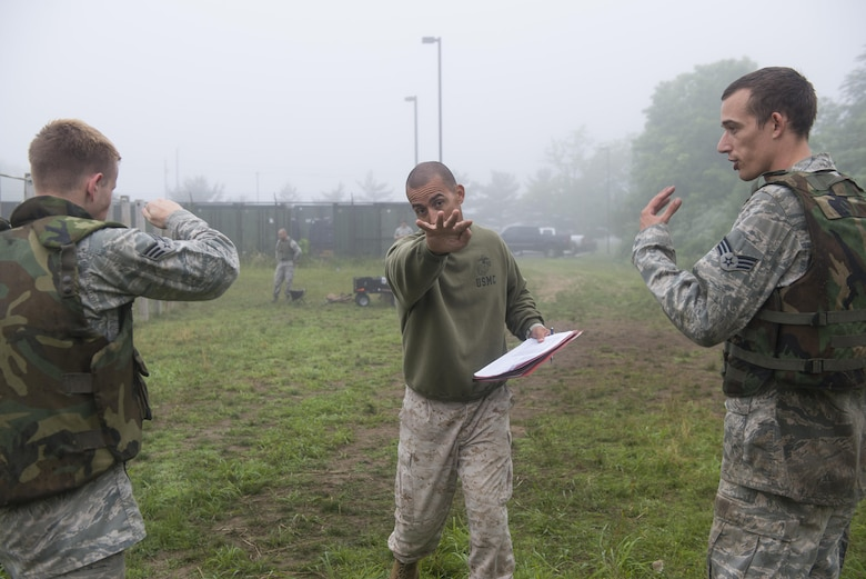 Marine Gunnery Sgt. Lucio Bernabe, assigned to the Marine Aircraft Group 49 and a Marine Corps Martial Arts Program course instructor, demonstrates the correct eye-gouge movement after a MCMAP tan belt class on Joint Base McGuire-Dix-Lakehurst, N.J., June 16, 2015. Ten Airmen took and passed the course. (U.S. Air Force photo/Airman 1st Class Joshua King)