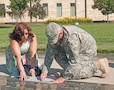 Jennifer Yllescas Winterbauer, sister of Capt. Robert Yllescas, makes a rubbing of her brother's name June 9 in Victory Park after a memorial rededication ceremony. Capt. Yllescas led Troop B, 6th Sqdn., 4th Cav. Regt., 3rd IBCT, 1st Inf. Div., when he was hit by a roadside bomb explosion in late 2008 near Combat Outpost Keating in Afghanistan. Yllescas succumbed to his wounds a month later at Bethesda Naval Medical Center.