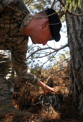 Tech. Sgt. Rian Hudson, 30th Security Forces Squadron NCOIC of confinement, conceals his homemade geocache, June 11, 2015, Vandenberg Air Force Base, Calif. Geocaching is a global game in which players conceal caches and upload the coordinates to a website for other players to find via Global Positioning System devices. (U.S. Air Force photo by Airman 1st Class Ian Dudley/Released)