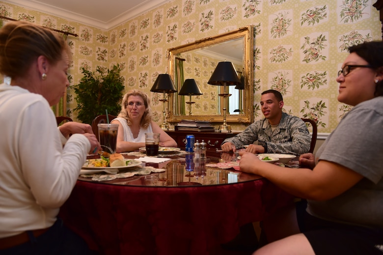 Team Buckley members enjoy dinner with those staying at the Fisher House June 17, 2015, in Aurora, Colo. Team Buckley members volunteered at the Fisher House to show support for veterans and their families. (U.S. Air Force photo by Airman 1st Class Luke W. Nowakowski/Released)