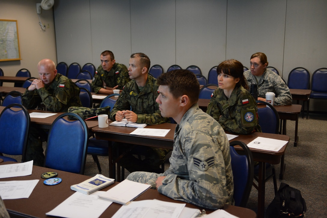 Members of the Polish Air Force receive their first briefing prior to entering the operations module at the 128th Air Control Squadron, Volk Field Air National Guard Base, Wisconsin, June 10, 2015. As part of the State Partnership Program, the four service members spent their time in the United States working beside 128 ACS Airmen. (U.S. Air National Guard photo by Staff Sgt. Andrea F. Rhode)