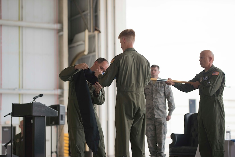 Colonel Fred Boehm places a protective case over the 17th Airlift Squadron's guidon flag officially retiring it during the squadron's inactivation ceremony June 25, 2015 at Joint Base Charleston, S.C. As part of the President's Defense Budget for FY15, one of Charleston's four active-duty C-17 flying squadron's was designated for inactivation. In attendance at the ceremony were many of the squadron's former commander's including Maj. Gen. (ret) Ron Ladnier, who commanded the squadron when it stood up as the first operational C-17 squadron. Boehm is the 437th Operations Group commander. (U.S. Air Force photo / Trisha Gallaway)