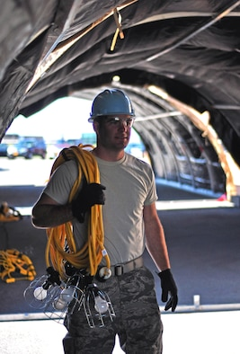 Senior Airman Colton Mattle, structural engineer, 914th Civil Engineer Squadron, prepares to hang lighting in at Niagara Falls Air Reserve Station, N.Y., on June 6, 2015. Mattle assists with preparation for weekend CES training exercises. (USAF photo by SSgt Richard D. Mekkri)