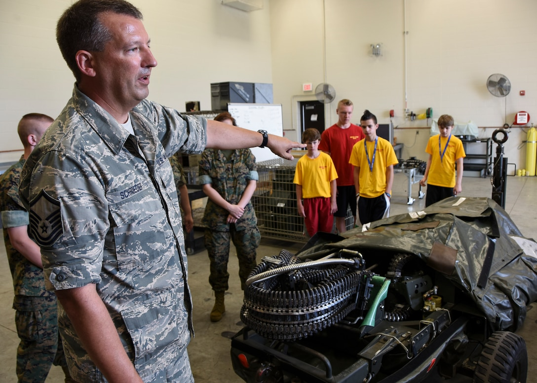 Master Sgt. Brett Schroeder, 114th Aircraft Maintenance Squadron munitions technician, briefs a group of students from Lincoln High School Marine Corps JROTC 2015 Drill Camp at Joe Foss Field during a base tour June 25. Schroeder explained the F-16 Fighting Falcon's 20mm Gatling gun system which fires at a rate of 6000 shots per minute. (National Guard photo by Staff Sgt. Luke Olson/Released)