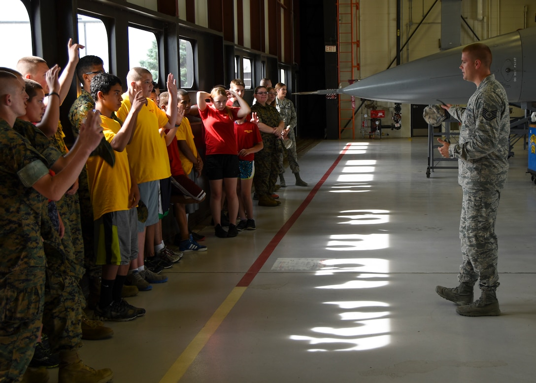 Tech. Sgt. Bo Ellefson, 114th Fighter Wing recruiter, engages a group of students from Lincoln High School Marine Corps JROTC 2015 Drill Camp during a base tour at Joe Foss Field, June 25, 2015. More than 40 students toured the 114th FW and were briefed about the many roles and specialized fields that make up the South Dakota Air National Guard. (National Guard photo by Staff Sgt. Luke Olson/Released)