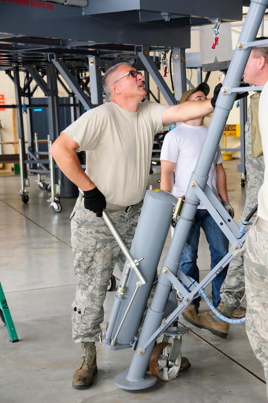U.S. Air Force Master Sgt. Kevin Mignosa, 145th Maintenance Squadron, ISO Dock leader, maneuvers a wing jack into place as other maintainers install new Isochronal Inspection (ISO) Aircraft Maintenance Platforms around a 145th Airlift Wing, C-130 Hercules aircraft at the North Carolina Air National Guard base, Charlotte Douglas International Airport, June 2, 2015. (U.S. Air National Guard photo by Master Sgt. Patricia F. Moran, 145th Public Affairs/Released)