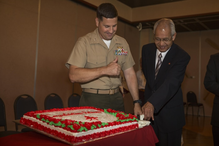 Col. Robert V. Boucher, left, commanding officer of MCAS Iwakuni, and Hiroshi Fujisawa, right, a tractor-trailer driver with Logistics, cut the cake at the retirement ceremony inside Club Iwakuni aboard Marine Corps Air Station Iwakuni, Japan, June 25, 2014. This ceremony is held annually to honor all of the Japanese contractors retiring within the year and to show the station's appreciation for their faithful service.