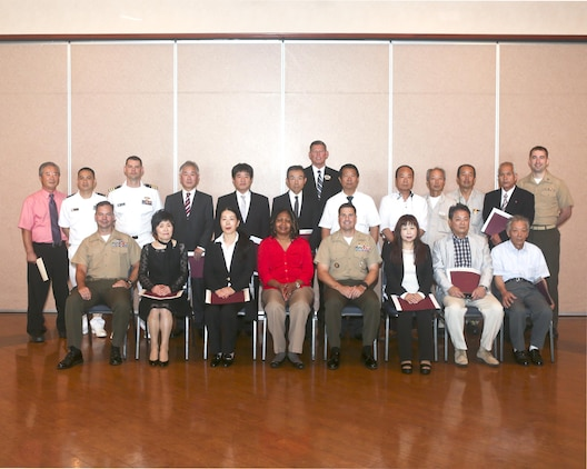 Department representatives, U.S. officials and retirees pose for a picture after the retirement ceremony at the Landing Zone inside Club Iwakuni aboard Marine Corps Air Station Iwakuni, Japan, June 25, 2014. This ceremony is held annually to honor all of the Japanese contractors retiring within the year and to show the station's appreciation for their faithful service.