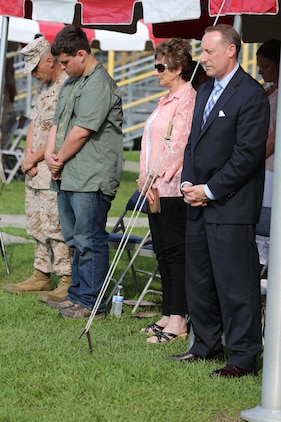 (From left to right) Chief Warrant Officer 5 Nicholas V. Vitale, Ground Combat Element Integrated Task Force Gunner, his son, Vincent, mother, Rita, and brother, John, bow their heads during the chaplain's invocation at Vitale's retirement ceremony June 18, 2015, at W.P.T. Hill Field, Marine Corps Base Camp Lejeune, North Carolina. Vitale retired after serving more than 30 years in the Marine Corps. (U.S. Marine Corps photo by Sgt. Alicia R. Leaders/Released)