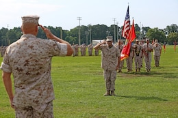 Chief Warrant Officer 5 Nicholas V. Vitale, center, Ground Combat Element Integrated Task Force Gunner, and the parade, salute Lt. Gen. Robert B. Neller, commander of Marine Corps Forces Command, in honoring the reviewing officer during Vitale's retirement ceremony June 18, 2015, at W.P.T. Hill Field, Marine Corps Base Camp Lejeune, North Carolina. Neller served as a mentor throughout Vitale's career, and was the reviewing officer for his ceremony. Vitale retired after serving more than 30 years of service in the Marine Corps. (U.S. Marine Corps photo by Alicia R. Leaders/Released)