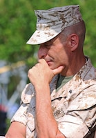 Chief Warrant Officer 5 Nicholas V. Vitale, Ground Combat Element Integrated Task Force Gunner, listens to the remarks of Lt. Gen. Robert B. Neller, as he talks about his time spent with Vitale in the Marine Corps and throughout the years during Vitale's retirement ceremony June 18, 2015, at W.P.T. Hill Field, Marine Corps Base Camp Lejeune, North Carolina. Neller served as a mentor throughout Vitale's career, and was the reviewing officer for his ceremony. Vitale retired after serving more than 30 years of service in the Marine Corps. (U.S. Marine Corps photo by Alicia R. Leaders/Released)