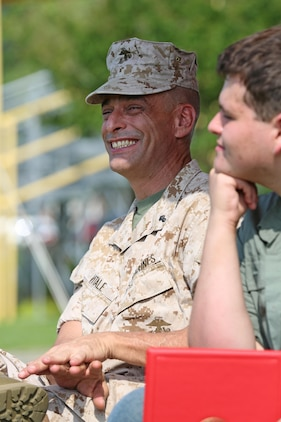 Chief Warrant Officer 5 Nicholas V. Vitale, Ground Combat Element Integrated Task Force Gunner, smiles as he listens to the remarks of Lt. Gen. Robert B. Neller during Vitale's retirement ceremony June 18, 2015, at W.P.T. Hill Field, Marine Corps Base Camp Lejeune, North Carolina. Neller served as a mentor throughout Vitale's career, and was the reviewing officer for his ceremony. Vitale retired after serving more than 30 years of service in the Marine Corps. (U.S. Marine Corps photo by Alicia R. Leaders/Released)