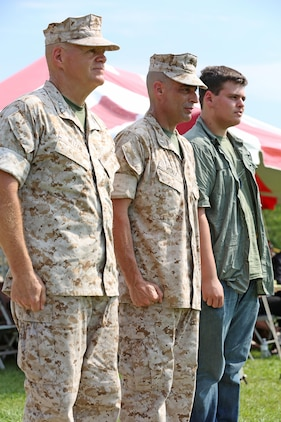 (From left to right) Lt. Gen. Robert B. Neller, commander of Marine Corps Forces Command, Chief Warrant Officer 5 Nicholas V. Vitale, Ground Combat Element Integrated Task Force Gunner, and his son, Vincent Vitale, stand in their positions during the pass and review of Vitale's retirement ceremony June 18, 2015, at W.P.T. Hill Field, Marine Corps Base Camp Lejeune, North Carolina. Neller served as a mentor throughout Vitale's career, and was the reviewing officer for his ceremony. Vitale retired after serving more than 30 years of service in the Marine Corps. (U.S. Marine Corps photo by Alicia R. Leaders/Released)