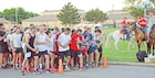 Runners set their watches outside of King Field House before the beginning of the Victory Week 10-Miler June 10 at 6:30 a.m.