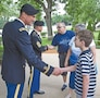 Evan Boldt, grandson of retired Air Force Lt. Col. John R. Godby, shakes hands with Col. Matthew R. Lewis, commander, 1st CAB, 1st Inf. Div., after a wreath-laying ceremony June 14 at the Eisenhower Presidential Library, Museum and Boyhood Home in Abilene, Kansas. Evan and his grandparents traveled more than 240 miles to witness the ceremony, which honored the Army general and president on the Army's 240th birthday.