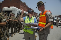 Mary B. Skarote, an exercise planner for the 2015 Parris Island hurricane exercise, discusses evacuation procedures with a Lima Company, 3rd Recruit Training Battalion, drill instructor June 24, 2015, on Parris Island, S.C. The practiced evacuation was part of a hurricane exercise that simulated the efforts needed to evacuate permanent personnel, recruits and equipment. After the week-long exercise, officials will review the outcome and apply any necessary changes to ensure MCRD Parris Island can continue making Marines regardless of what mother nature throws at the Lowcountry.