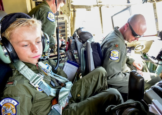 Ethan Hoffman sits in the crew chief seat of a C-130H Hercules aircraft here next to Maj. Brian Hodor, a pilot with the 757th Airlift Squadron, shortly after taxiing down the runway June 24, 2015. Twelve-year-old Ethan was sworn in as an honorary second lieutenant as he became the 910th Airlift Wing's 62nd Pilot for a Day, receiving a day of military experiences and mementos. Ethan was selected for the program by Akron Children's Hospital in Boardman where he is treated for Bartter Syndrome, a rare kidney disease he has had since birth. (U.S. Air Force photo/Eric M. White)