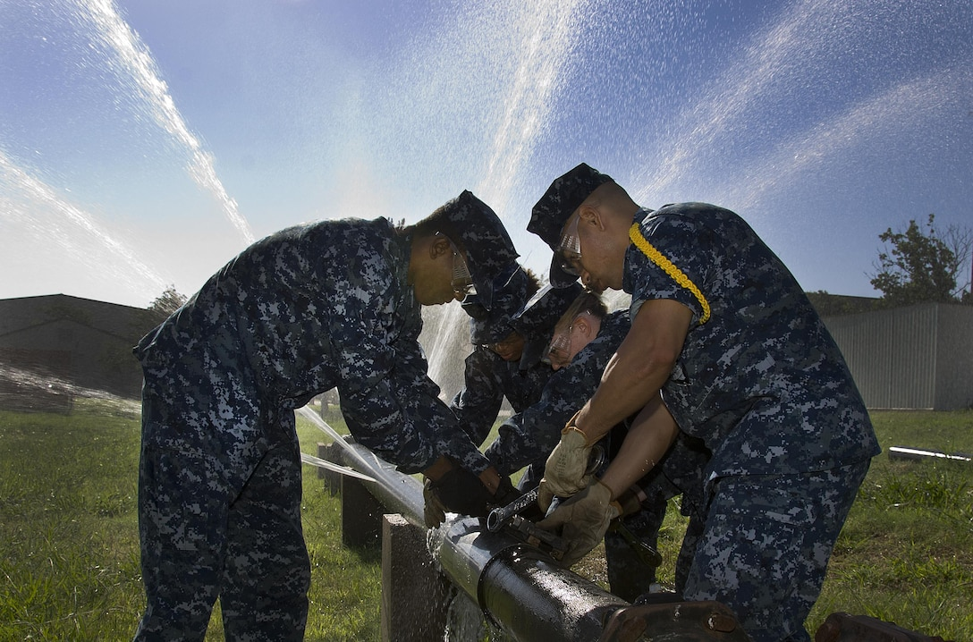 U.S. Navy Sailors assigned to the 366th Training Squadron for training perform emergency repairs to a simulated water main in the Water and Fuel Systems Maintenance Apprentice course at Sheppard Air Force Base, Texas, June 24, 2015. Students in the course learn how to install, inspect, maintain, troubleshoot, modify, and repair potable and waste water systems ensuring they comply with environmental and safety regulations. (U.S. Air Force photo/Danny Webb)