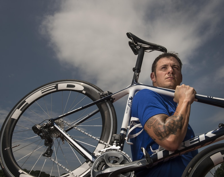 Senior Master Sgt. Jason Hoover carries his bicycle between competitions during the 2015 Department of Defense Warrior Games in Quantico, Va., June 23, 2015. The Warrior Games features athletes from throughout the Defense Department who compete in Paralympic-style events for their respective military branches. (U.S. Air Force photo/Staff Sgt. Vernon Young Jr.)