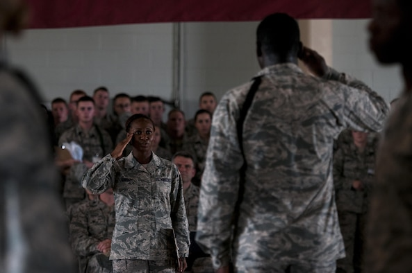 U.S. Air Force Tech. Sgt Curtrell L. Gibson, 17th Training Wing Airman Leadership School instructor, salutes a drill lead from the 316th Training Squadron signifying the end of the regulation drill circuit inside the High Bay at the Louis F. Garland Fire Academy on Goodfellow Air Force Base, Texas, June 22, 2015. The 316th TRS drill team won both the regulation drill and the exhibition drill circuits. (U.S. Air Force photo by Senior Airman Scott Jackson/Released)